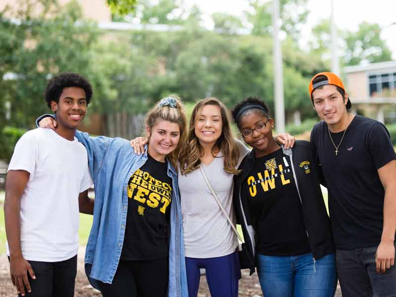 A group of students posing together in front of the campus breezeway.